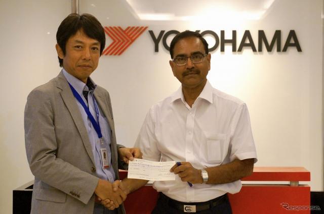 インド赤十字社のピー・シー・パルティハリ副長官(右)に義援金を手渡す藤津聡YIN社長《画像 横浜ゴム》