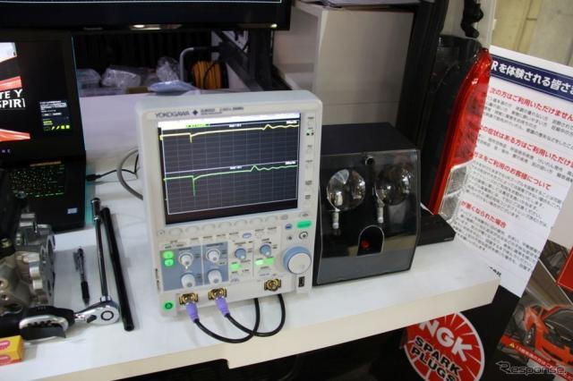 新品プラグと劣化プラグの放電を比較している≪撮影:中尾真二≫