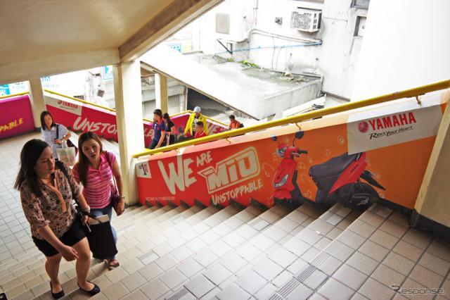 ヤマハモニュメント駅の階段にも、主力車種『MIO』の広告が《撮影 宮崎壮人》