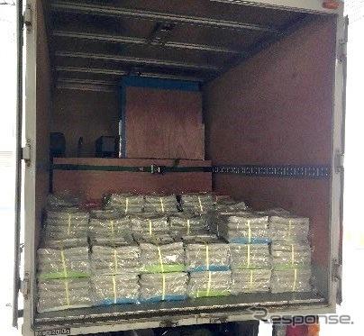 奥に段ボールで梱包された食塩、手前に読売新聞が積まれたトラック荷台《写真 日本マクドナルド、読売新聞グループ本社》